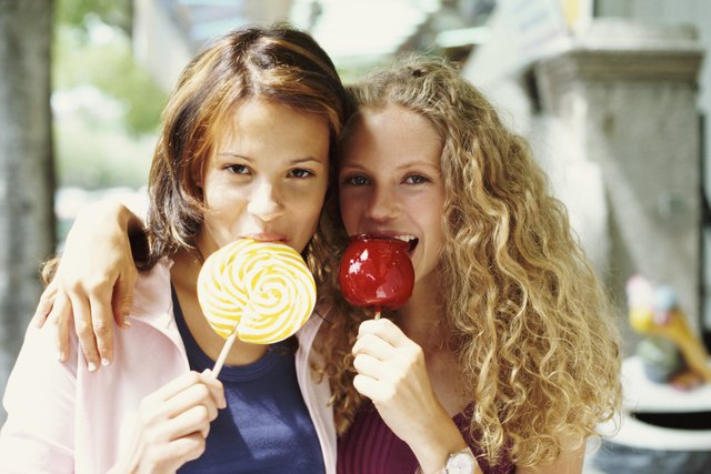 Two Female Teenagers Eating a Toffee Apple and a Lolly