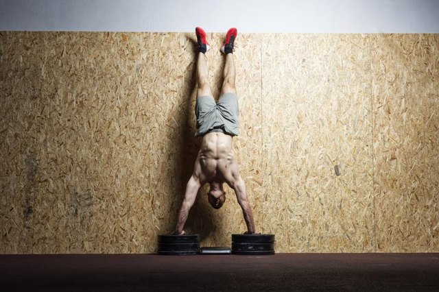 Man performing handstand on the wall