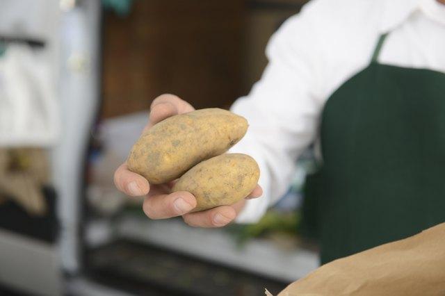 Mature man holding potatoes at market stall
