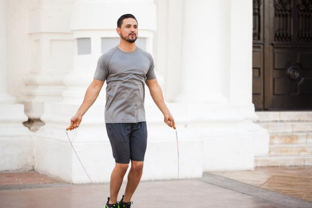 Good looking young man jumping a rope and exercising outdoors in the city
