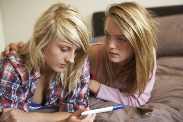 Teenage Girls Lying On Bed Looking At Pregnancy Testing Kit