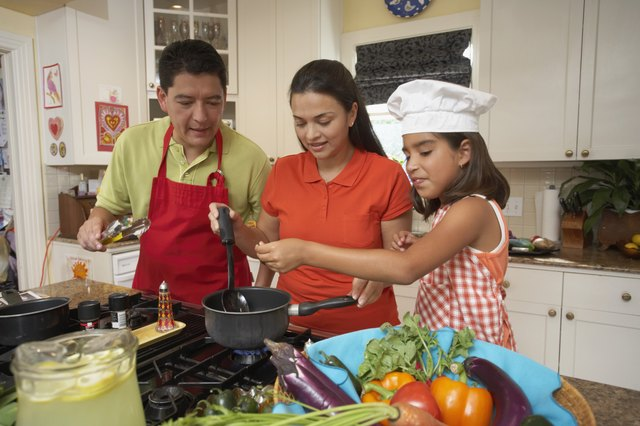 Mid adult couple cooking with their daughter