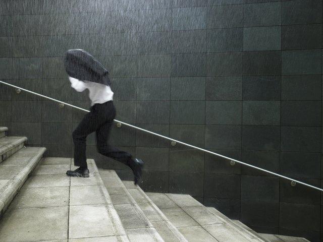 Businessman running up steps, sheltering under jacket, side view