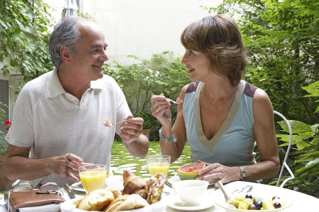 Mature couple having breakfast in garden, smiling at each other