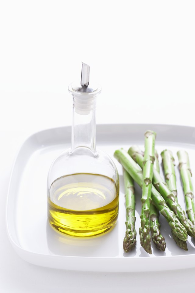 Asparagus and olive oil on plate, close-up