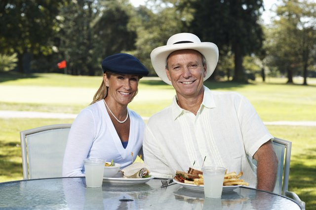 Mature couple sitting at outdoor table on golf course, portrait