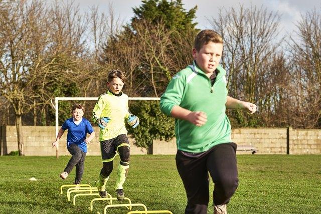Children's football team running drills