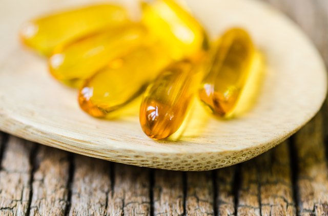Fish oil on wooden spoon with wooden texture background