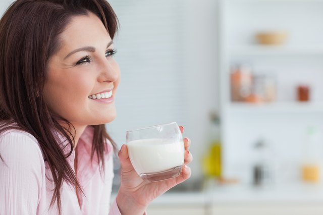 Side view of woman with glass of milk