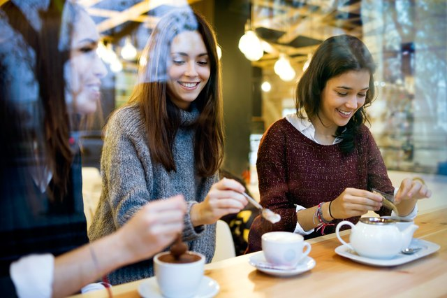 Three young beautiful women drinking coffee at cafe shop.