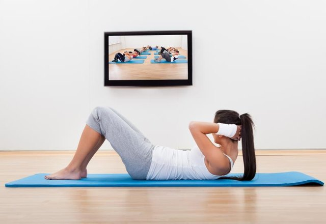 Athletic barefoot young woman working out at home lying on a mat doing liftups and head raises while watching and participating in a class