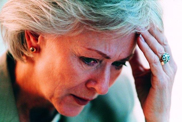 Worried businesswoman resting head in hand