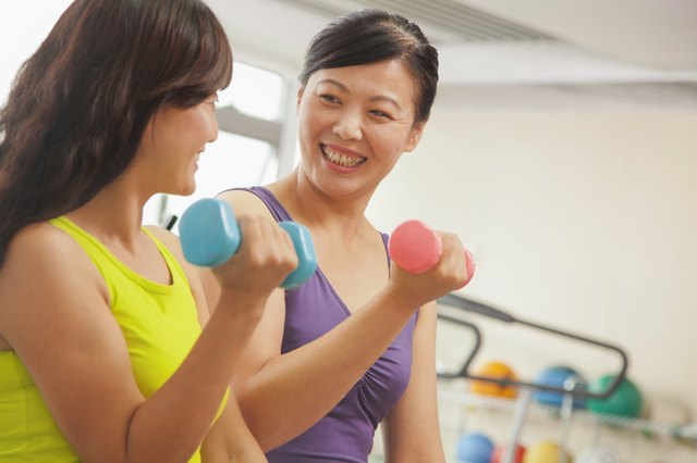 Two mature women lifting weights in the gym