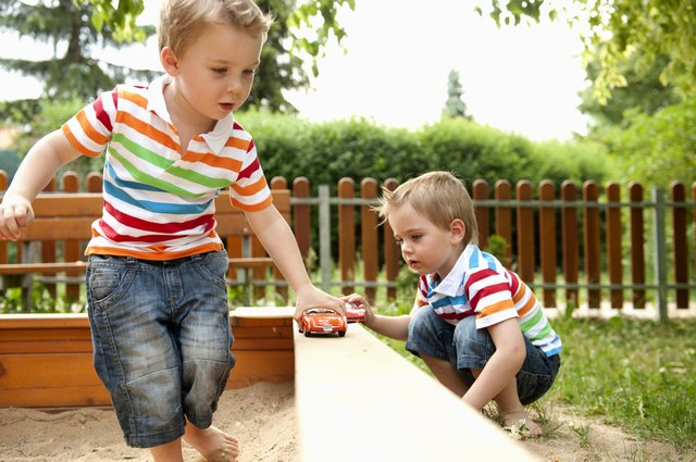 Twin brothers playing in sandpit with toy cars