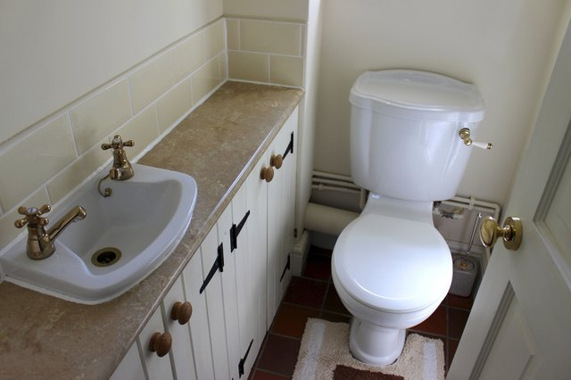 Image of country style cloakroom toilet, basin and storage cupboards