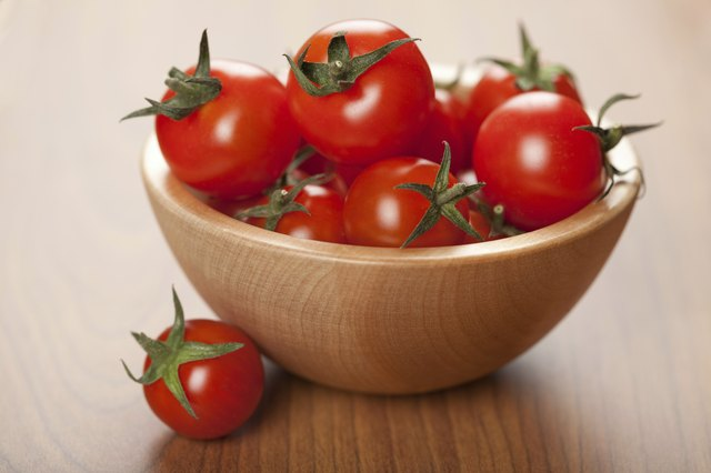 ripe tomatoes in wooden bowl