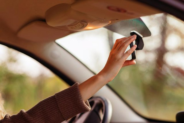 the girl in the car adjusts the rear view mirror