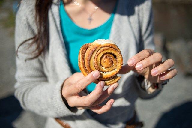 A lady holding a cinnamon bun