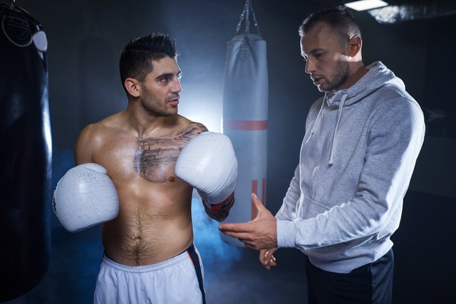 Male coach guiding mid adult boxer