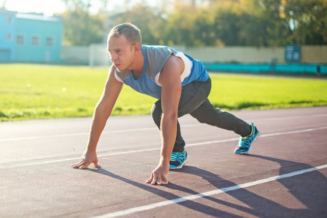 Athletic man standing in  posture ready to run on a