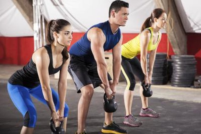 Three people working out with kettlebells in a gym gym