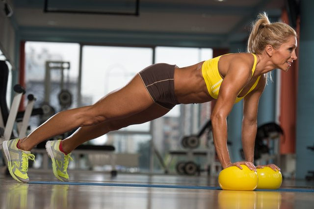 Woman Exercising Push Ups On Yellow Balls