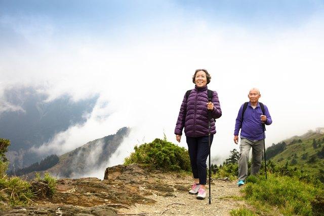 happy asian senior couple hiking on the mountain