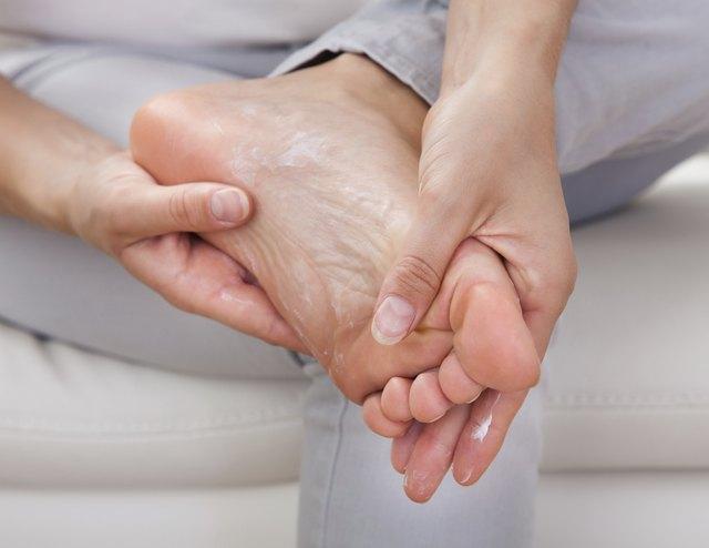 Woman applying cream on feet