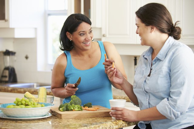 Two Overweight Women On Diet Preparing Vegetables in Kitchen