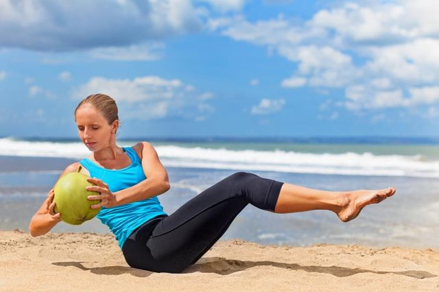 Fit woman exercising stomach muscle on ocean beach. Doing crunches.