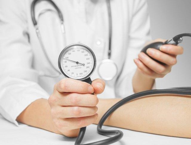 Doctor measures blood pressure by sphygmomanometer