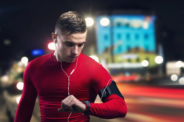 Man in red jogging at night and looking at his watch