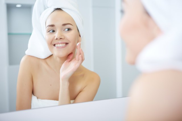 Beautiful Young Woman applying facial moisturizing cream.Skincare concept