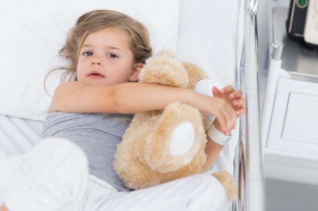 Cute girl hugging teddy bear in hospital bed