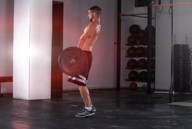 Handsome and muscular young man practice exercises in crosfit club with great weight