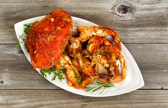 Spicy cooked crab on white plate with rustic wood