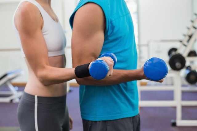 Fit couple exercising with blue dumbbells