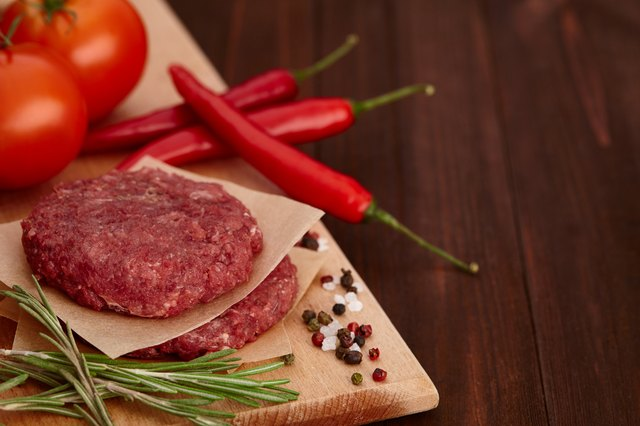 Raw meat for burgers with spices on wooden board