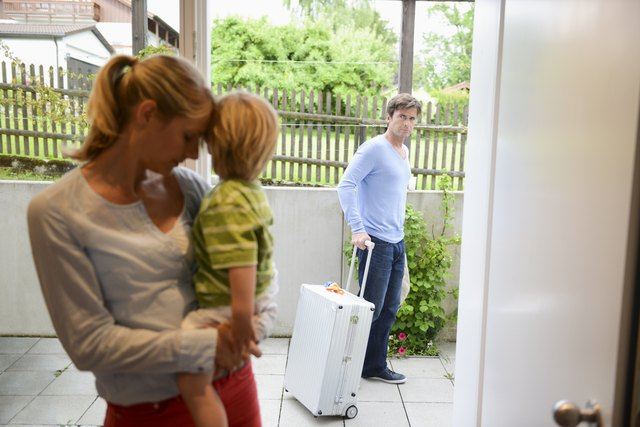 Mid adult woman consoling son as father leaves