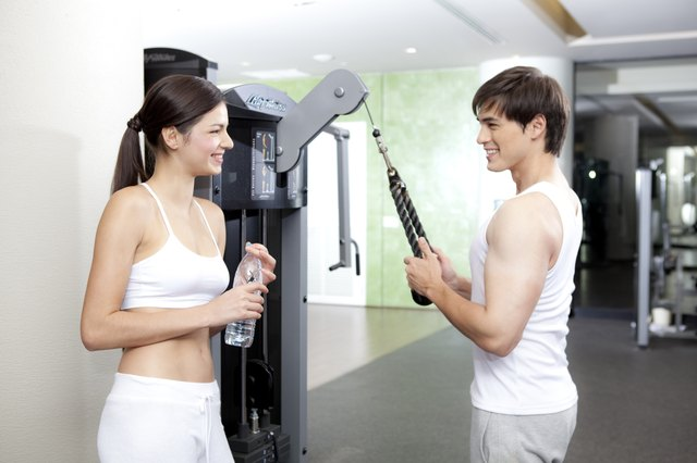 A man working out on his arms while woman is looking