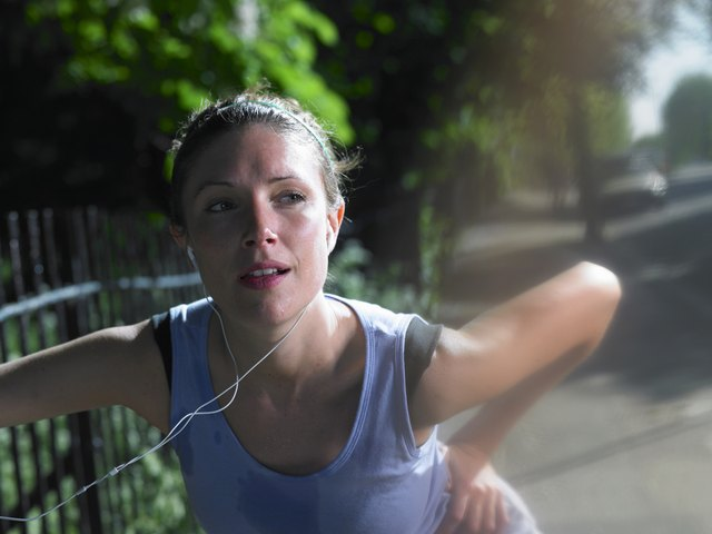 Young woman stretching by fence on street