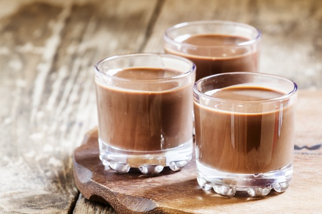 Liquid chocolate in a glass on the old wooden background