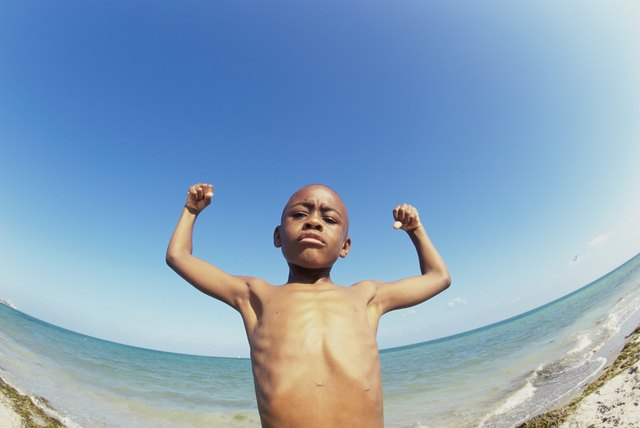 Low angle view of a boy flexing his muscles on the beach