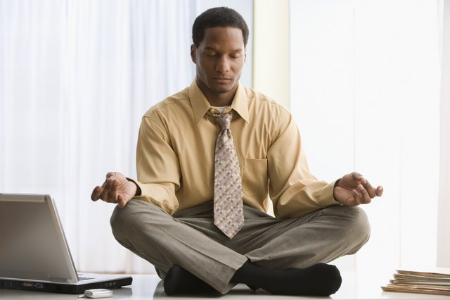 African American businessman meditating on desk