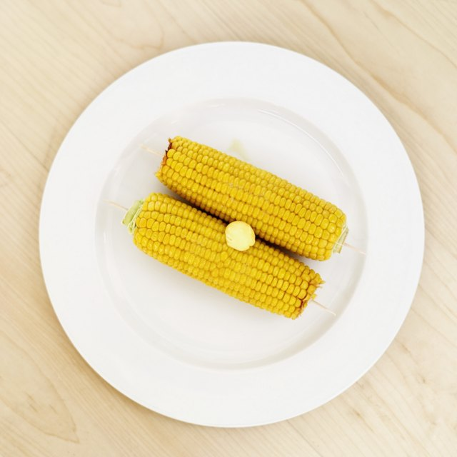 Elevated view of two corncobs topped with butter