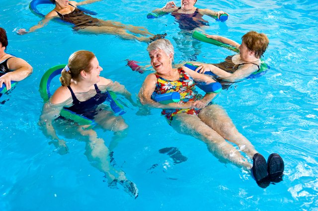 Two women floating on water aerobics noodles