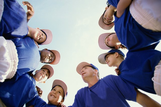 Low angle view of baseball players standing in a huddle with their coach