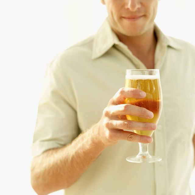 mid section view of a mid adult man holding a glass of beer