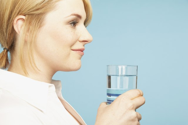 Studio shot of young woman holding glass of water