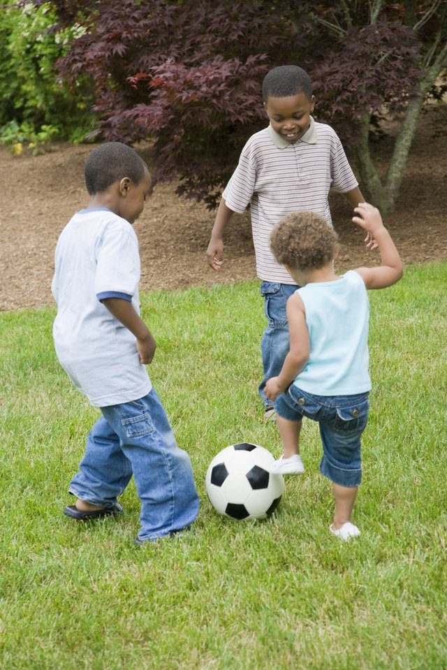 Two boys playing soccer with their sister